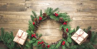 Christmas wreath made of spruce branches with gifts on wooden board. Flat lay. Top view. stock images