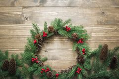 Christmas wreath made of spruce branches with holly berries on wooden board. Flat lay. Top view. Copy space royalty free stock image