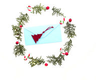 Christmas wreath made of thuja twigs, red wild rose fruits with green envelop and Xmas decoration cane in the middle Stock Photography