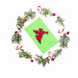 Christmas wreath made of thuja twigs, red wild rose fruits with green envelop and Xmas decoration cane in the middle Stock Photo