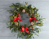 Christmas wreath with mistletoe. On wood board. Christmas decoration royalty free stock photo