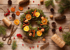 Christmas wreath with natural decorations, pine cones spruce, nuts, candied fruit on a rustic wooden table. Christmas decorations royalty free stock photo