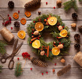 Christmas wreath with natural decorations, pine cones spruce, nuts, candied fruit on a rustic wooden table. Royalty Free Stock Photography