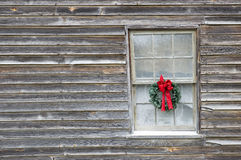 Christmas Wreath On Old Farmhouse. Horizontal shot of a Christmas wreath hanging in a window on an old farmhouse. Lots of copy space Royalty Free Stock Photos