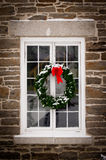 Christmas Wreath on Old Window Pane. A green spruce Christmas wreath with red ribbon hangs in the middle of an old, snow covered window pane set in stone wall royalty free stock photos