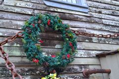 Christmas Wreath Outdoors. A christmas Wreath on an old weathered boathouse Stock Photography