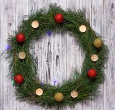 Christmas wreath of pine branches with candles on a white wooden background, Christmas balls, copy space royalty free stock images