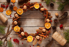 Christmas wreath of pine branches and cones, decorated with candied orange, nuts, cinnamon on old vintage table. Royalty Free Stock Photos