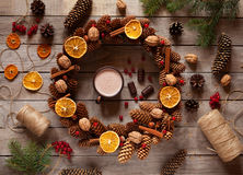 Christmas wreath of pine branches and cones, decorated with candied orange, nuts, cinnamon on old vintage table. Stock Photos