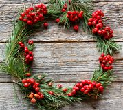 Christmas wreath of pine branches and red Rowan on wooden background. Copy space. Christmas wreath of pine branches and red Rowan on wooden background Royalty Free Stock Photo