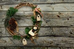 Christmas wreath. With pine cones, houses and snowman on a wooden wall Stock Photos