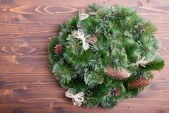 Christmas wreath of pine needles with cones on a brown board Stock Images