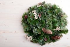 Christmas wreath of pine needles with cones on light board Royalty Free Stock Photo