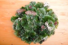 Christmas wreath of pine needles with cones on a yellow board Royalty Free Stock Photos