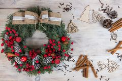 Christmas wreath of pine with red elements on a white wooden background. Christmas wreath on a white wooden background. Christmas wreath of pine with red royalty free stock photo