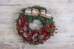 Christmas wreath of pine with red elements on a white wooden background Christmas wreath on a white wooden background. Christmas wreath of pine with red elements stock photo