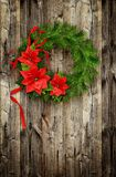 Christmas wreath from pine twigs and ponsettia flowers Stock Photos