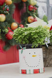 Christmas Wreath and Plant in Snowman Container Royalty Free Stock Photos