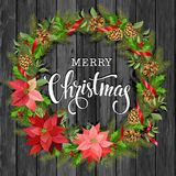 Christmas wreath of poinsettia, fir branches, cones, holly and other plants on a wooden background. Cover, invitation Stock Image