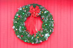Christmas Wreath on red. Christmas Wreath with ornaments on red wood wall Royalty Free Stock Images