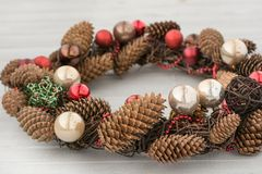 Christmas wreath with red balls and cones on board. Christmas wreath with red balls and cones on wooden board Royalty Free Stock Photography