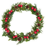 Christmas Wreath. With red baubles, holly, mistletoe, ivy, pine cones and cedar leaf sprigs over white background royalty free stock image