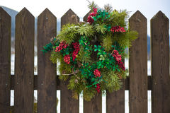 Christmas wreath with red berries hanging on wooden fence Royalty Free Stock Photos
