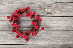 Christmas wreath from red berries. On wooden background Royalty Free Stock Photos