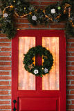 Christmas wreath on red door stock images