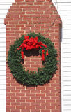 Christmas Wreath with Red Ribbon on Brick Chimney Stock Images