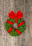 Christmas wreath with red ribbon on wooden background Stock Image