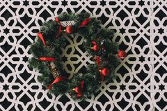 Christmas wreath with red ribbons hanging on the white wall with carved ornament. Christmas wreath with red ribbons hanging on the wall with carved ornament royalty free stock photography