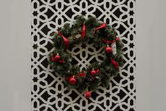 Christmas wreath with red ribbons hanging on the white wall with carved ornament. Christmas wreath with red ribbons hanging on the wall with carved ornament royalty free stock images