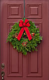 Christmas wreath on a red wooden door Stock Photography