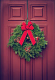 Christmas wreath on a red wooden door. Christmas wreath hanging on a red wooden door. Vintage filter effects royalty free stock image