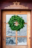Christmas wreath on a rustic front door. Christmas wreath on a rustic wooden front door royalty free stock photos