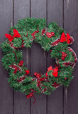 Christmas wreath on a rustic wooden front door. Christmas wreath on a rustic wooden black front door Royalty Free Stock Photo