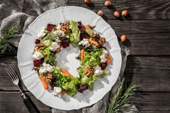 Christmas wreath salad with fresh carrots, beets, nuts, cheese, lettuce and arugula on plate on rustic wooden table. royalty free stock photos