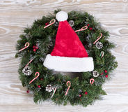 Christmas wreath and Santa cap with lights and candy canes on wh Royalty Free Stock Photo