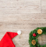 Christmas wreath and   Santa claus hat  on wooden background Stock Photography