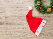Christmas wreath and   Santa claus hat  on wooden background Royalty Free Stock Images