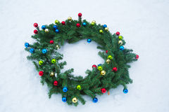 Christmas Wreath in the Snow. Evergreen Christmas wreath decorated with tiny, colorful ornaments in the snow Royalty Free Stock Photos