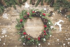 Christmas wreath of spruce branches with holly berries on wooden board. Flat lay. Top view. Copy space stock images