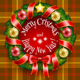 Christmas wreath on a tan plaid background Royalty Free Stock Image
