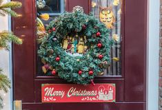 Christmas wreath with text Merry Christmas. Attached on a Dutch front door Royalty Free Stock Photo