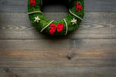 Christmas wreath traditional, classic type. Wreath made of spruce branches and red ribbons on dark wooden background top stock image