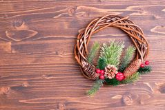 Christmas wreath of twigs with pine needles and cones on a brown Stock Photos