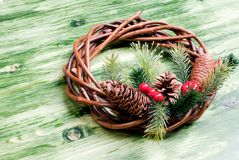 Christmas wreath of twigs with pine needles and cones on a green Royalty Free Stock Photography