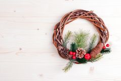 Christmas wreath of twigs with pine needles and cones on light b Royalty Free Stock Photo