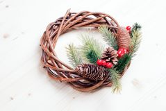 Christmas wreath of twigs with pine needles and cones on light b Royalty Free Stock Photography